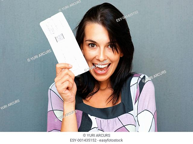 Woman holding up airplane ticket and smiling