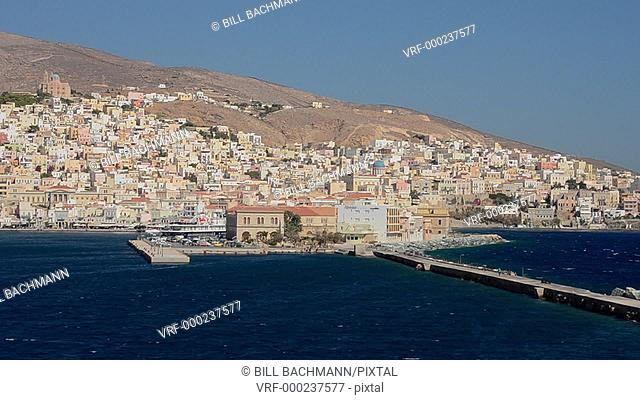Syros Grece in Greek Islands from ferry of white houses and village on cliffs in Mediterranean Ocean
