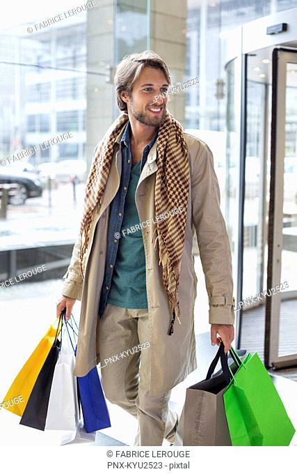 Man carrying shopping bags and smiling
