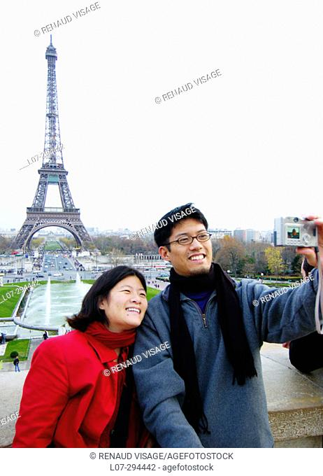 Man and woman photographing themselves with digital camera in front of the Eiffel Tower. Paris. France
