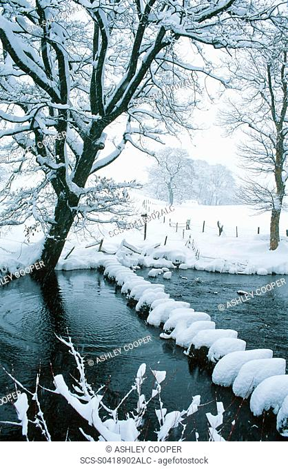 Snow on the Stepping stones across the River Rothay in the Vale of Rydal in the Lake District UK
