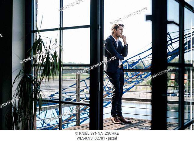 Businessman standing on balcony, looking shocked