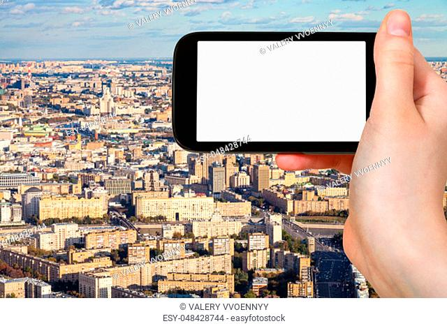 travel concept - tourist photographs of aerial view of center and southwest of Moscow city from observation deck in autumn on smartphone with empty cutout...