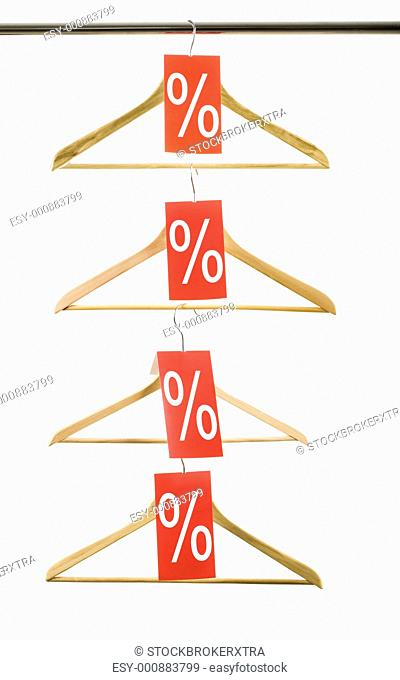 Photo of four hangers with holiday discounts in vertical order over white background