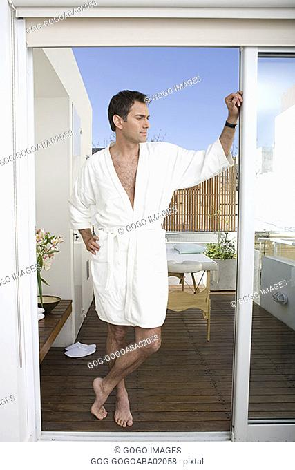 Man standing on porch in his bathrobe