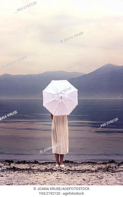 a girl with a parasol at the beach