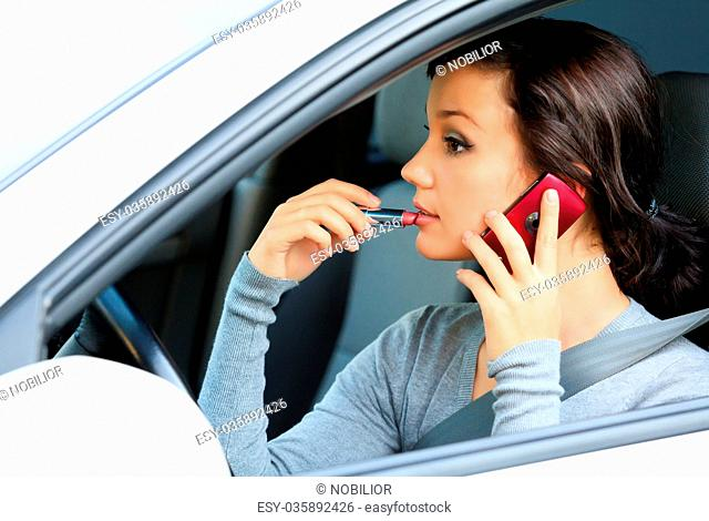 Female driver talking by mobile telephone and doing make-up