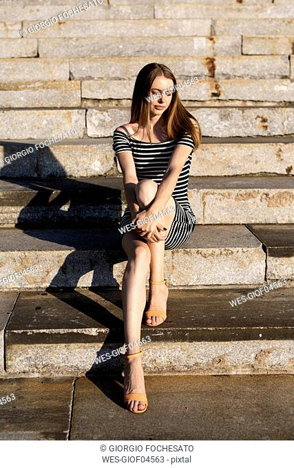 Portrait of young woman sitting on stairs enjoying sunset