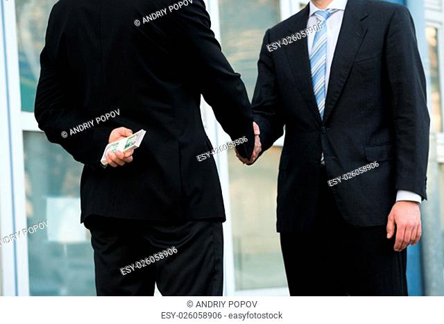 Midsection of dishonest businessman holding dollar bundle while shaking hands with partner outdoors