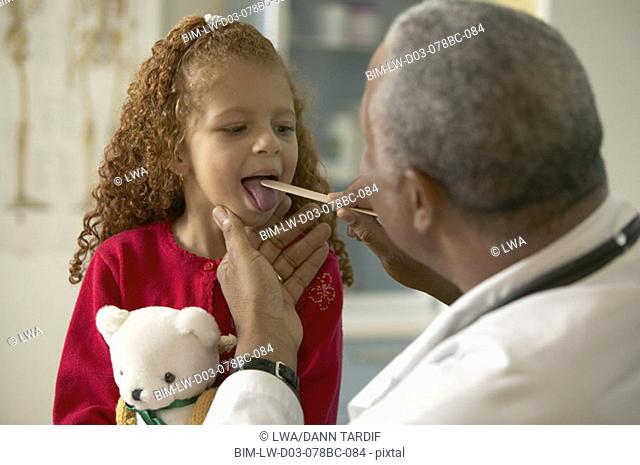 Male doctor checking throat of little girl