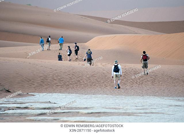 Tourists walking along the sand dunes in the Namib-Naukluft National Park in Namibia, Africa