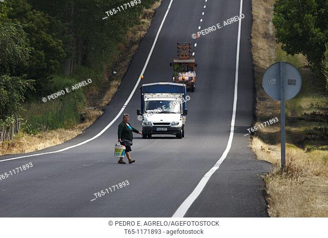 Woman crossing, road marking painting, LU-633 road in Paradela, Sarria, Province of Lugo, Galicia, Northern Spain