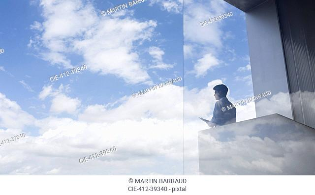 Pensive businessman standing on modern balcony looking at blue sky and clouds