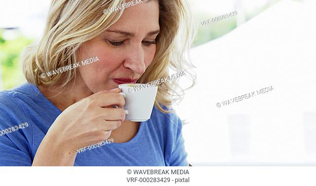 Smiling woman having a cup of tea at home