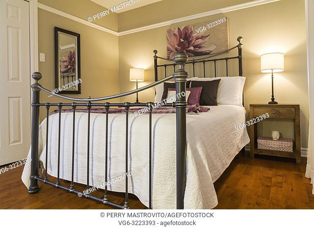 Queen size bed with white bedspread and antique wrought iron headboard and footboard in guest bedroom on the upstairs floor inside a contemporary cottage style...