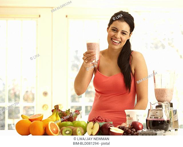 Hispanic woman making fruit smoothie