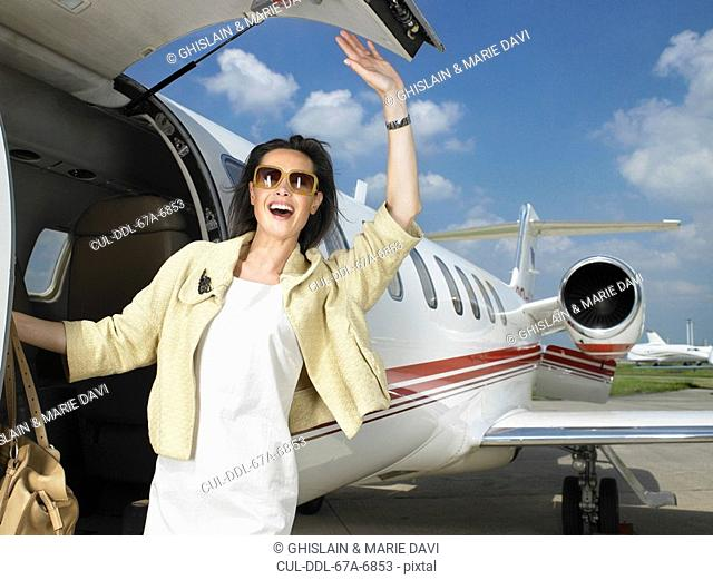 Happy female exiting corporate Jet