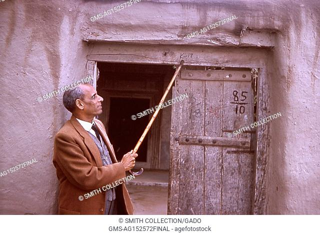 Photograph of a public health official, Nurahmed, using a cane to point at the front door of a house, Gujarat, India, 1964. Image courtesy CDC. ()