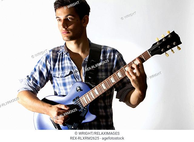 Teenager playing electric guitar music instrument
