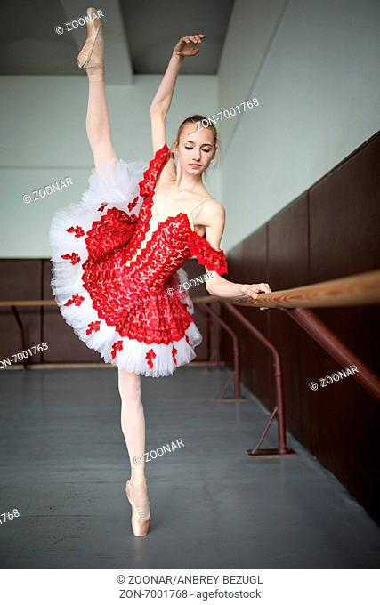 Young ballerina standing on one leg on your toes in pointe and doing stretching, lifting the leg up high. Model holds hands behind the barre