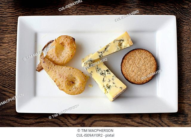 Overhead view of stilton, poached pears and crackers on cheese board