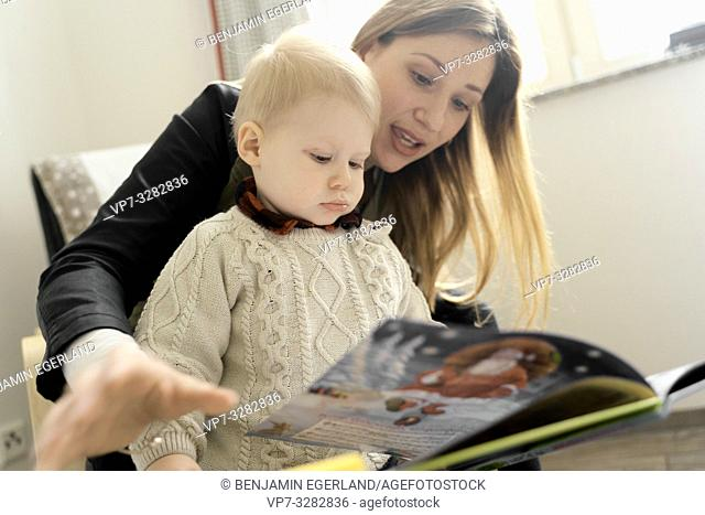 mother with baby toddler child reading book at home, in Cottbus, Brandenburg, Germany