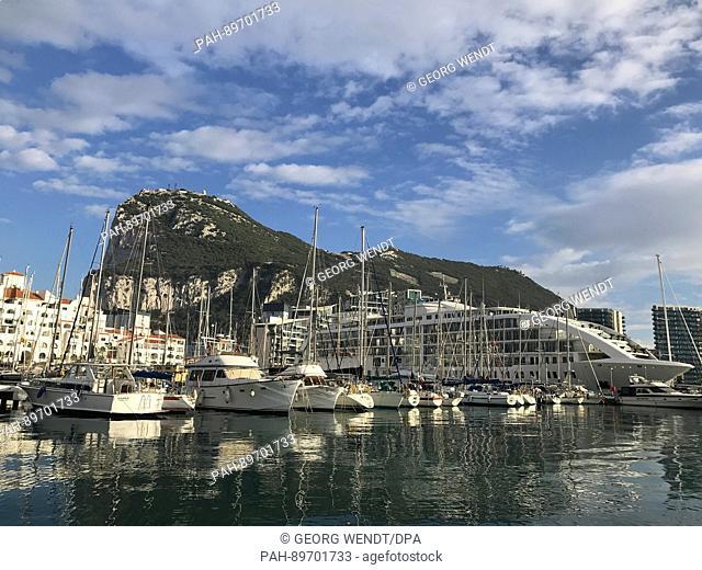 Sailboats and a cruise ship at Marina Ocean Village in Gibraltar, La Línea de la Concepción, Spain, 22 October 2016. In the background is the Rock of Gibraltar