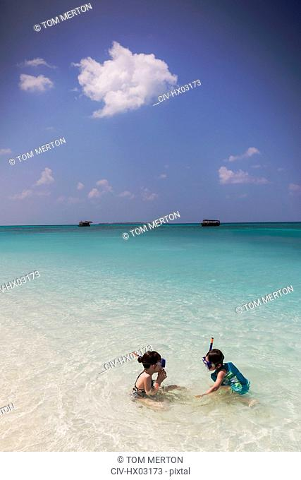 Boy and girl brother and sister snorkeling in sunny blue tropical ocean