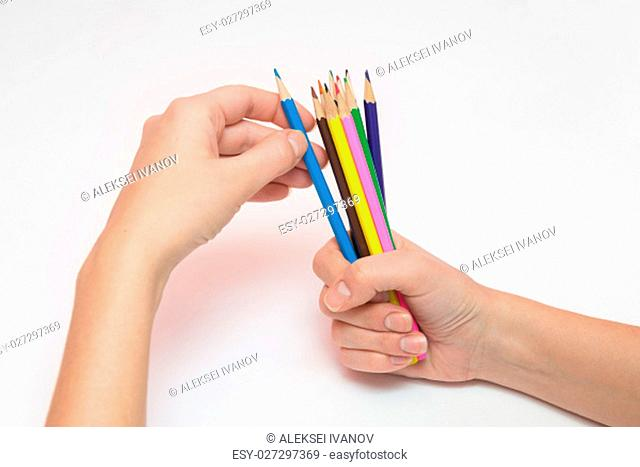 Female hand holding a fist around a dozen pencils, the other hand selects the desired color