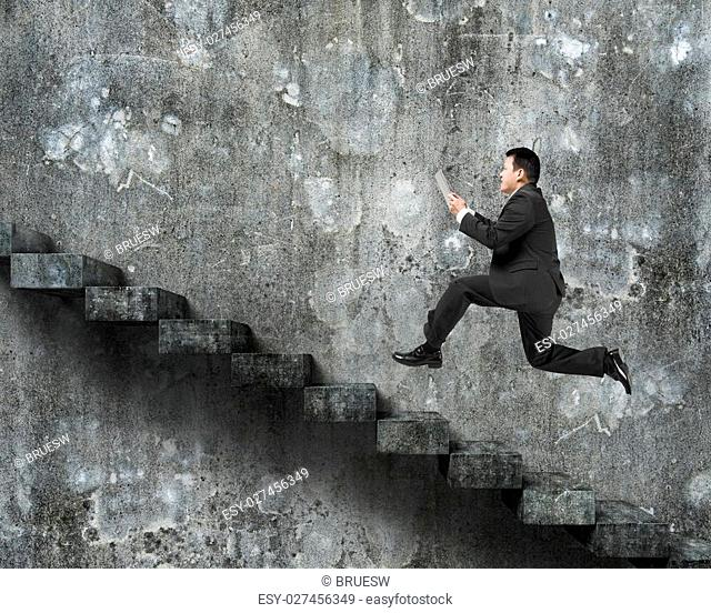 Man using tablet running on old dirty concrete stairs with wall background