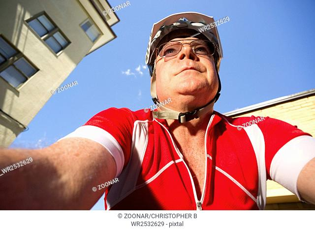 Mature Man Rides Bicycle Downtown Seen from Low Angle