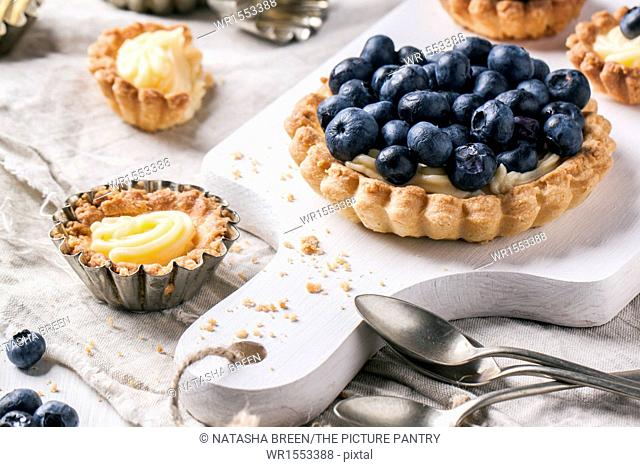 Blueberry tarts served on white cutting board with vintage teaspoons