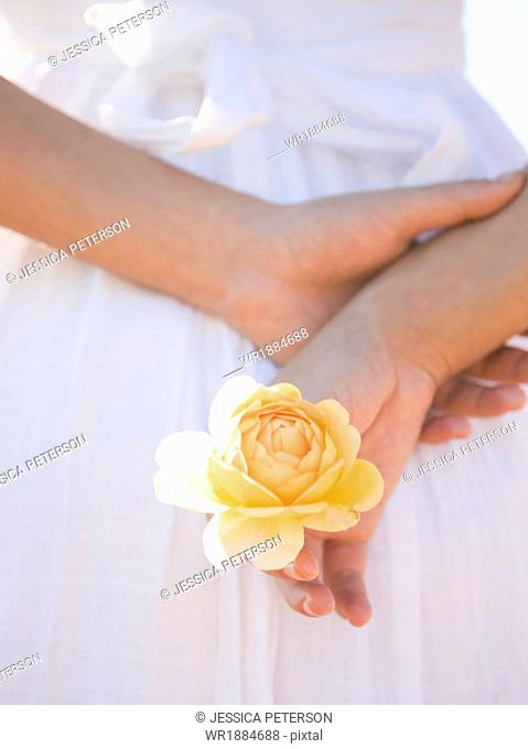 USA, Utah, Lehi, mid section of teenage girl (16-17) holding rose behind back