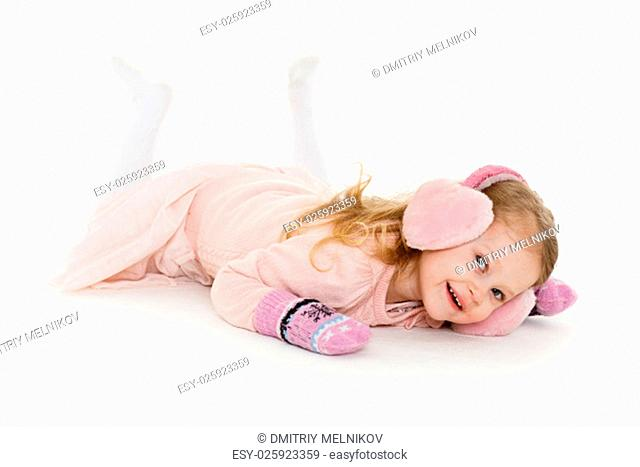 Little happy pretty girl in winter clothes lies on a white background. 3 year old