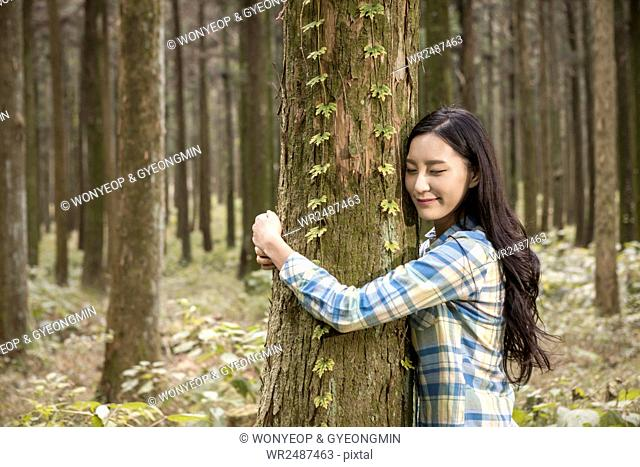 Side view portrait of young woman hugging a tree closing eyes in forest