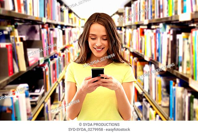 teenage student girl using smartphone at library