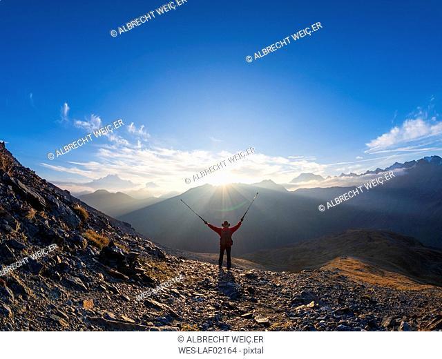 Border region Italy Switzerland, cheering senior man with hiking poles in mountain landscape at Piz Umbrail