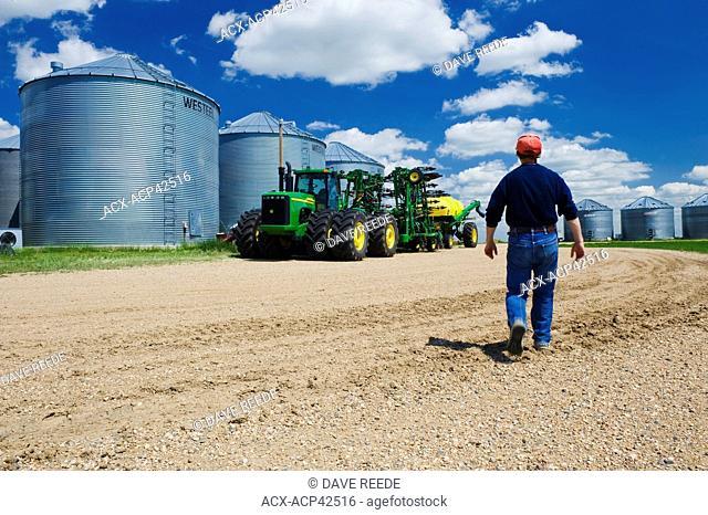 A man walks toward seeding equipment in farmyard near Torquay Saskatchewan, Canada