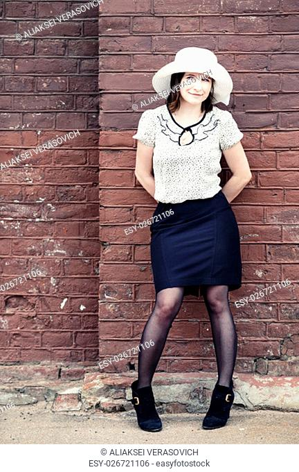 Pretty young woman in a white hat, blouse and black skirt, posing outdoor against brick wall background. Toned photo with copy space