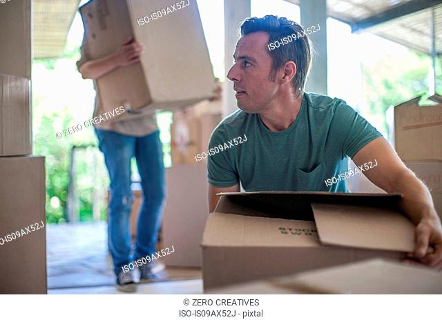 Moving house: couple lifting cardboard boxes
