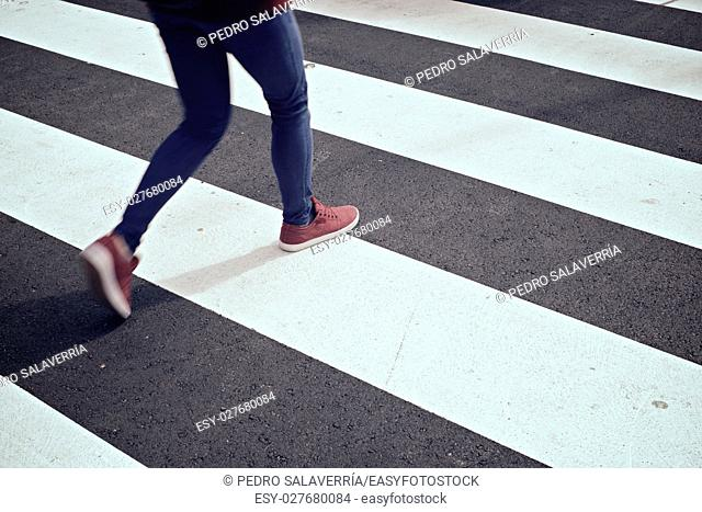 Young woman crossing a zebra crossing. Zaragoza, Aragon, Spain