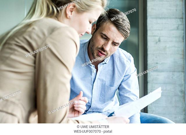 Two colleagues in office talking