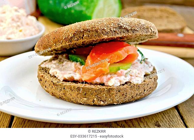 Sandwich of rye bread with cream, cucumber, dill and salmon on a plate on a wooden boards background
