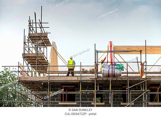 Worker working on roof of building
