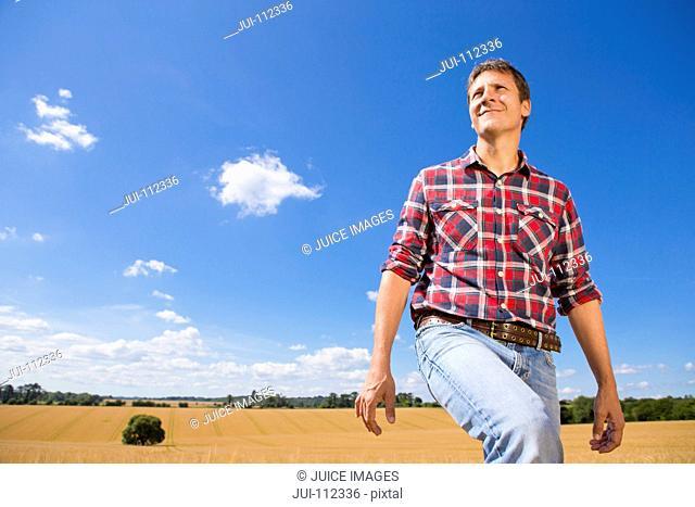 Smiling farmer walking in sunny rural barley crop field in summer