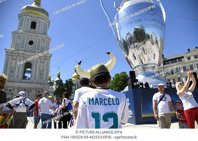 26 May 2018, Ukraine, Kiev: A Real Madrid supporter wearing a Marcelo jersey walks past a blow-up trophy in front of Saint Sophia's Cathedral