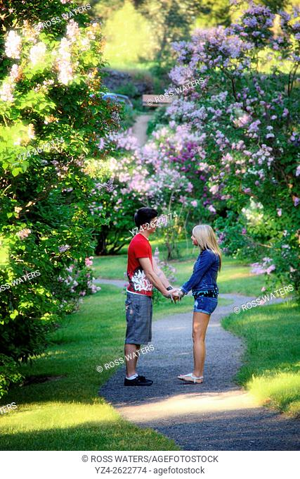 A young couple together outdoors in a lilac garden