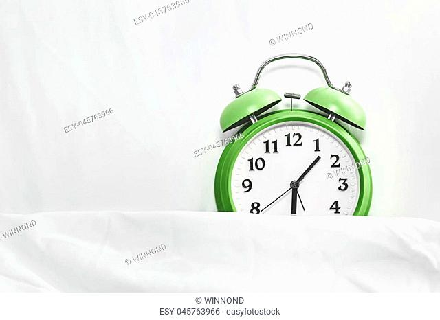 alarm clock on bed sheets