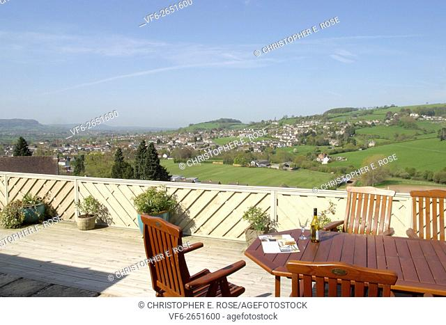 UK garden patio terrace decking with table and chairs and a view over open countryside. For Editorial Use Only