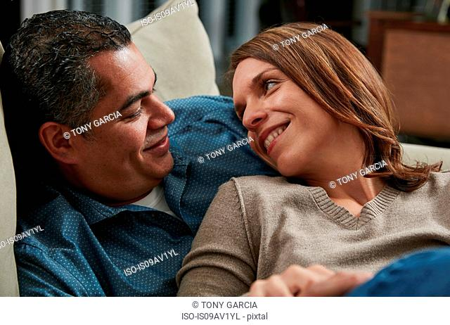 Head and shoulders of couple snuggling on sofa face to face smiling